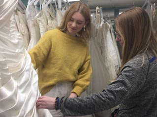 Two young women assessing a bridal gown